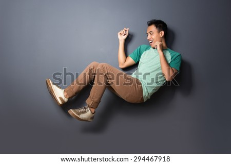 portrait of young man floating and act like fall over isolated on dark background - stock photo