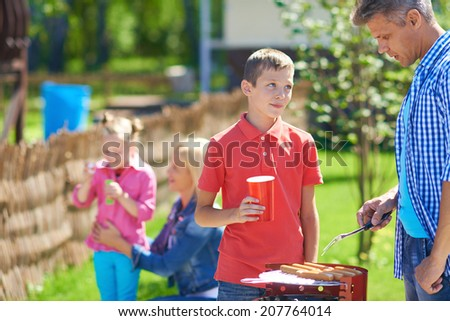 Portrait of young man frying sausages and talking to his son in the countryside at weekend - stock photo