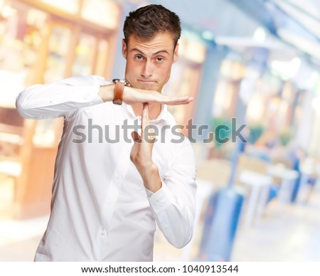 Portrait Of Young Man Gesturing Time Out Sign, Indoor