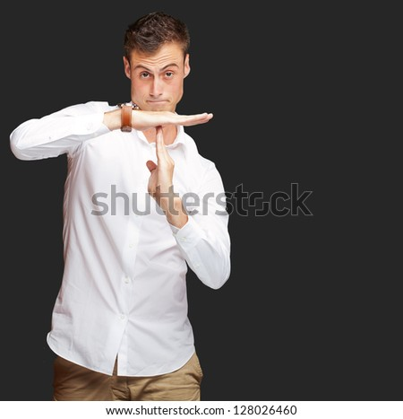 Portrait Of Young Man Gesturing Time Out Sign On Black Background - stock photo