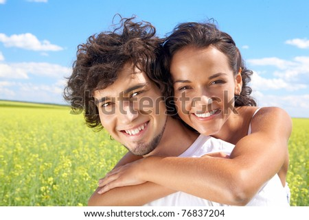 Portrait of young man giving beautiful woman piggyback in the field - stock photo