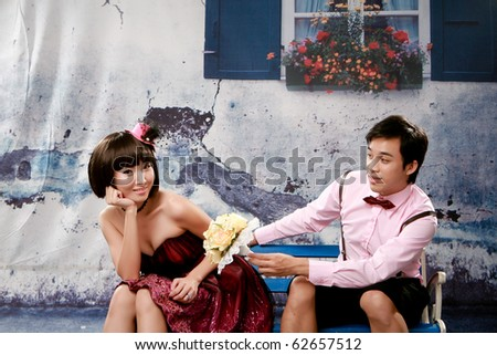 Portrait of young man giving bouquet to young girl in lovely action - stock photo