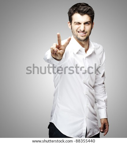 portrait of young man handsome doing good symbol over grey background - stock photo