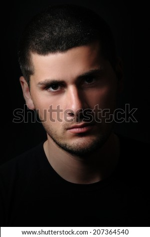 Portrait of young man handsome face over black background