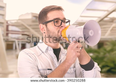 Portrait of young man handsome shouting using megaphone - stock photo