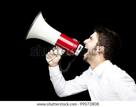 portrait of young man handsome shouting using megaphone over black background - stock photo
