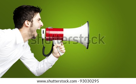 portrait of young man handsome shouting using megaphone over green background - stock photo