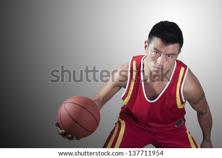 Portrait of young man holding a basketball - stock photo