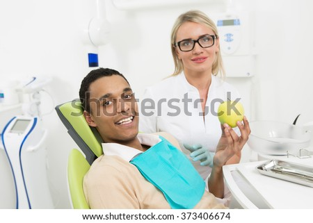 Portrait of young man holding a green apple and looking at the camer while his dentist lady sitting on the background at the dentist's office. - stock photo