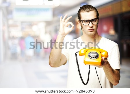 portrait of young man holding a vintage telephone and gesturing at crowded place - stock photo