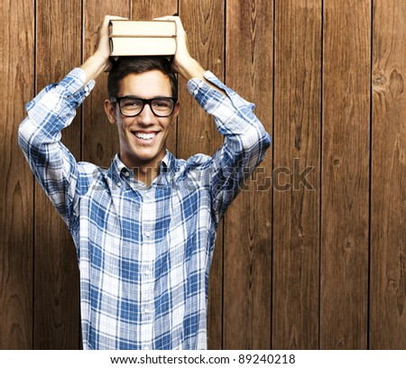 portrait of young man holding books on his head against a wooden wall - stock photo