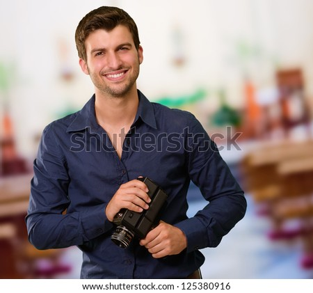 Portrait Of Young Man Holding Camera, Indoors