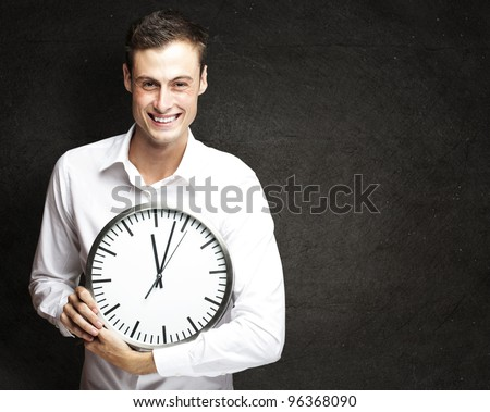 portrait of young man holding clock against a grunge background - stock photo