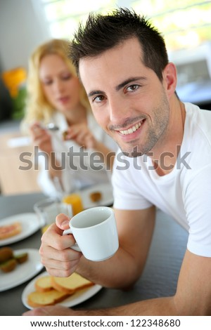 Portrait of young man holding cup of coffee - stock photo