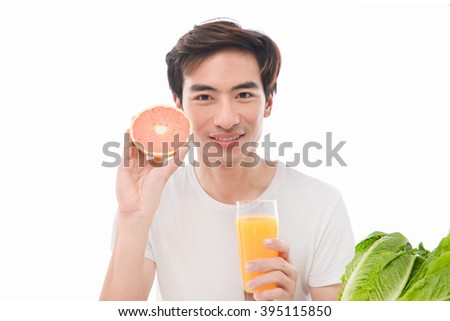 Portrait of young man holding glass of orange juice,grapefruit - stock photo