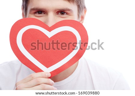 Portrait of young man holding paper heart