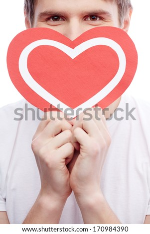 Portrait of young man holding paper heart - stock photo