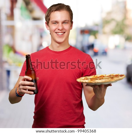 portrait of young man holding pizza and beer at street - stock photo