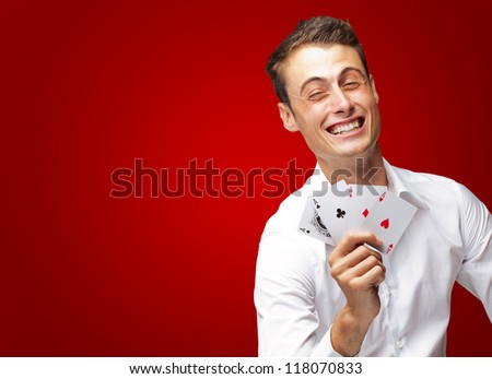 Portrait Of Young Man Holding Poker Cards Isolated On Red Background