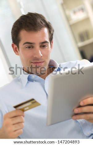 Portrait of young man holding tablet pc and credit card.indoor