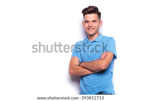 portrait of young man in blue polo shirt posing in white isolated studio background with hands crossed while looking at the camera