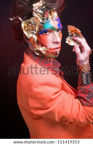 Portrait of young man in creative image with eccentric visage and in stylish cloth.