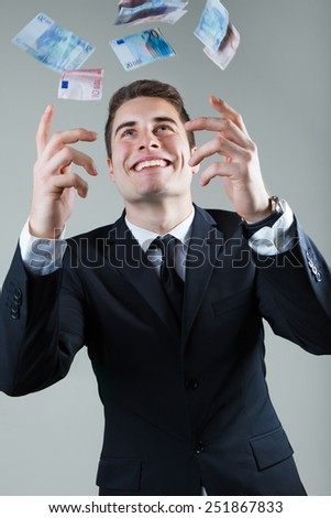 Portrait of young man in formalwear throwing money.