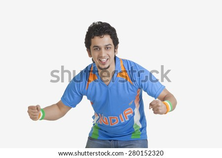 Portrait of young man in Indian cricket team jersey cheering with clenched fists over white background