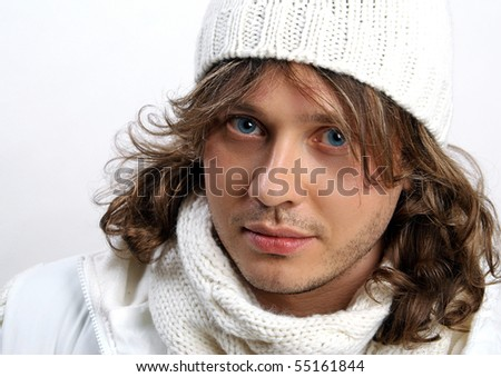 Portrait of young man in knitted hat and scarf on white background in the studio - stock photo
