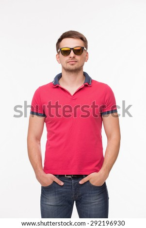 Portrait of young man in pink T-shirt with his arms in pockets. Man in fashionable sunglasses posing on white background.