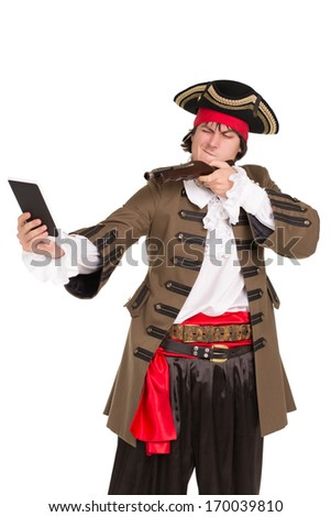 Portrait of young man in pirate costume aiming in the tablet. Isolated - stock photo