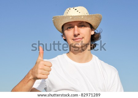 Portrait of young man in straw hat giving ok hand sign