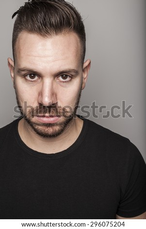Portrait of young man in studio setting and casual outfit - stock photo