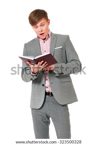 Portrait of young man in suit looking very shocked with notepad, isolated on white background  - stock photo