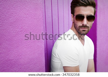Portrait of young man in sunglasses against purple wall - stock photo