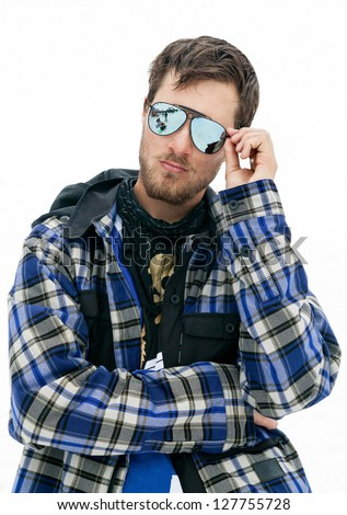 Portrait of young man in sunglasses at ski resort in mountains - stock photo