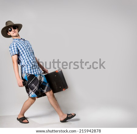 Portrait of young man in sunglasses with a suitcase in hand. Man in a hat with a phone in his hand. - stock photo