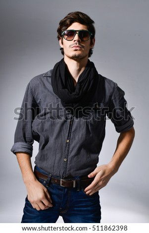 Portrait of young man in sunglasses with scarf â??light background