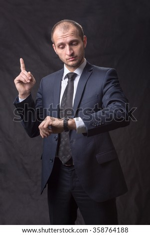 Portrait of young man in tie looking at his watch - stock photo