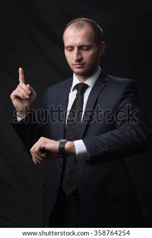 Portrait of young man in tie looking at his watch