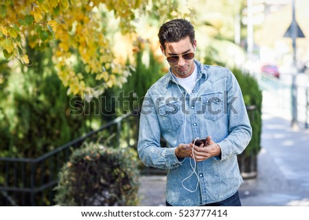 Portrait of young man in urban background listening to music with headphones. Guy wearing casual clothes and aviator sunglasses with a smartphone.