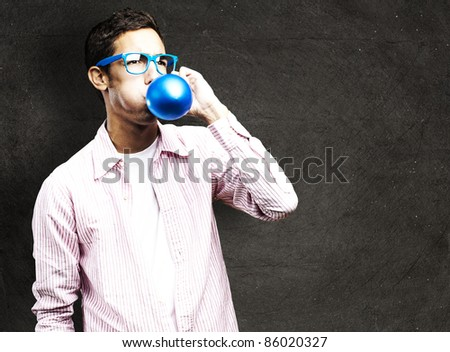 portrait of young man inflating a balloon against a grunge wall - stock photo