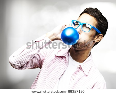 portrait of young man inflating a blue balloon in a house