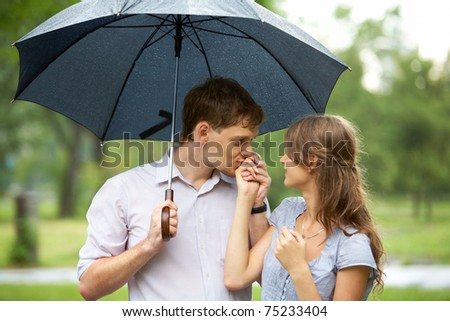 Portrait of young man kissing girl?s hand under umbrella outdoors - stock photo