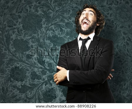 portrait of young man laughing against a grunge wall
