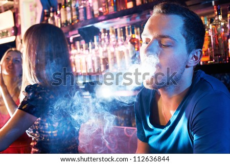 Portrait of young man letting smoke out of mouth while smoking hookah - stock photo