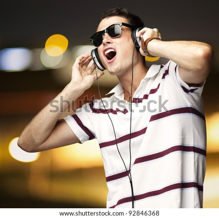 portrait of young man listening music with headphones and singing at a city by night