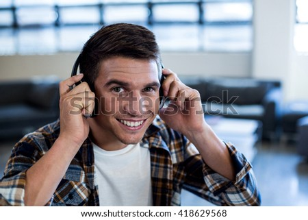 Portrait of young man listening to music with headphone in the office