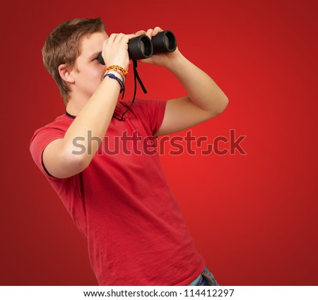portrait of young man looking through a binoculars over red background