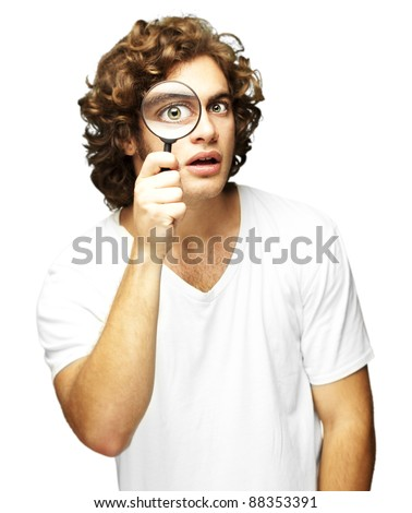 portrait of young man looking through a magnifying glass against a white background - stock photo